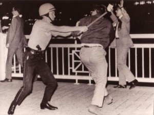 Jim Peipert getting thwacked by a Chicago police officer, Michigan Avenue Bridge, on the night before the start of the Democratic National Convention, Chicago, 1968